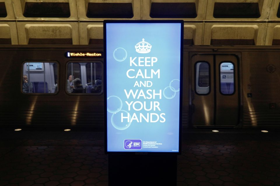 "An electronic sign displaying the message ""Keep Calm and Wash Your Hands"" is seen on display inside the Court House subway metro station in the Court House neighborhood of Arlington, Virginia"